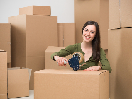 sealing tape: young caucasian woman sealing a cardboard box with adhesive tape. moving home