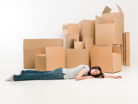 homeownership: young woman lying on the floor, exhausted after packing