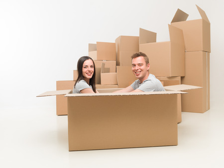 moving box: couple sitting in a box, having fun after moving in new home Stock Photo