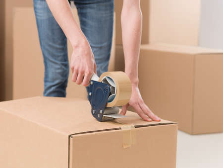 tape: close-up of female sealing cardboard box with adhesive tape Stock Photo