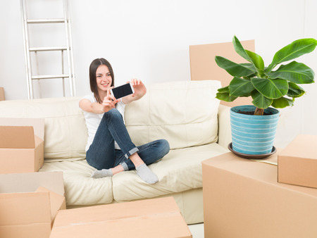homeownership: young woman sitting on sofa after moving in new house, taking a selfie with her phone Stock Photo
