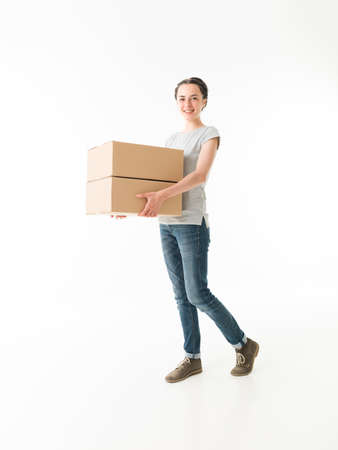 moving: young cauacsian woman carrying moving boxes, on white background