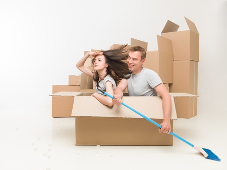 young couple sitting in a box pretending they are in a boat, paddeling with a broom