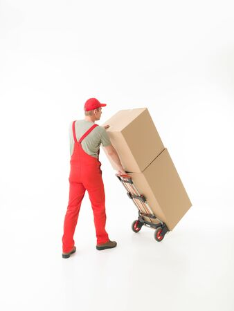 push cart: rear view of delivery man holding push cart loaded with cardboard boxes, on white background. copy space available