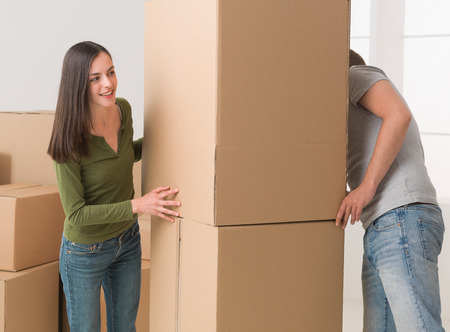 hide and seek: young couple playing hide and seek around cardboard boxes while moving house Stock Photo