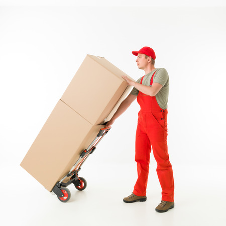 push cart: delivery man holding push cart loaded with cardboard boxes, on white background Stock Photo