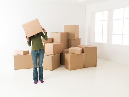 head home: woman moving in new house, having fun hiding her head in cardboard box