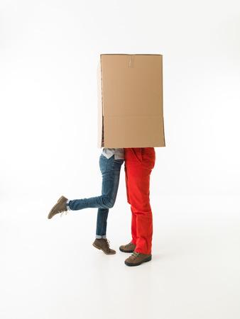 parejas enamoradas: pareja abrazándose y besándose, siendo cubierto por caja grande. en el fondo blanco