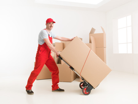 hand truck: full length of young caucasian deliveryman with hand truck, transporting cardboard boxes. moving house
