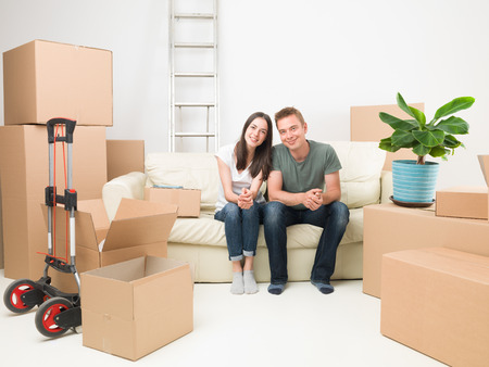 homeownership: happy couple sitting on sofa after moving in new house