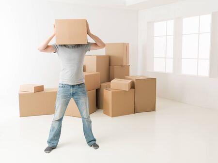 frustration: man hiding his head in cardboard box, standing in new apartment, despair gesture
