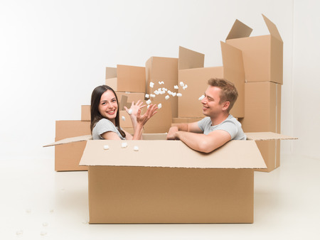 packing material: couple sitting in a box playing with packing material, having fun after moving in new home Stock Photo