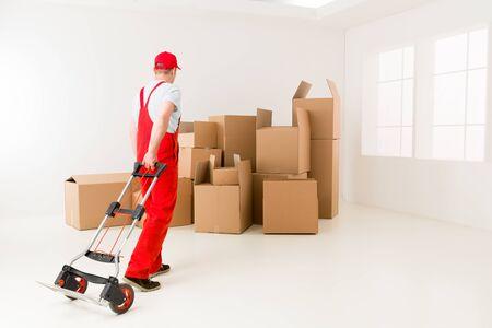 deliveryman: fattorino caucasico in uniforme rossa che tiene camion di mano, sempre pronto a caricare scatole di cartone
