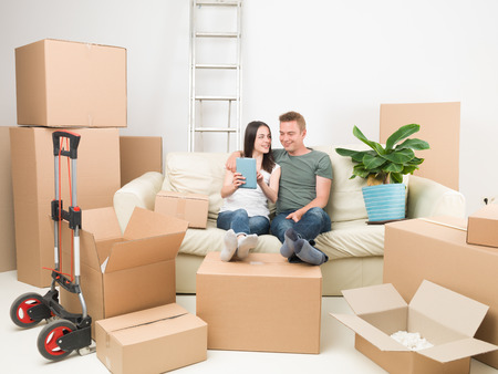 moving house: couple on sofa talking about decorations after moving in new house