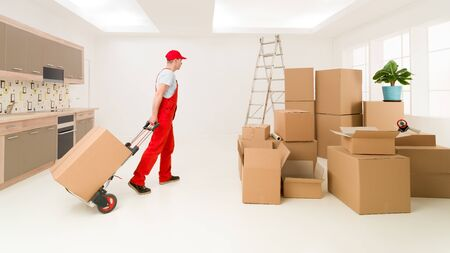 handtruck: caucasian deliveryman in red uniform holding hand truck, delivering boxes to new house