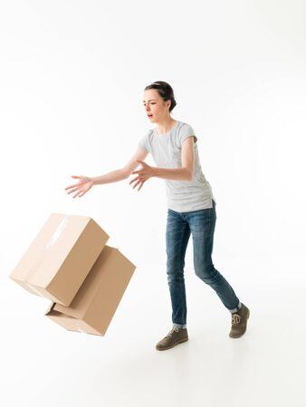 maldestro: goffo giovane donna caduta scatole in movimento e di intervento. su sfondo bianco