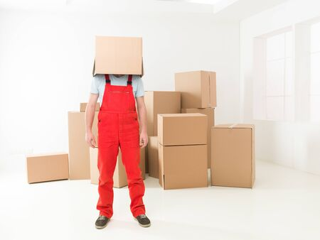 deliveryman: front view of deliveryman standing in new house with box covering his head. copy space available