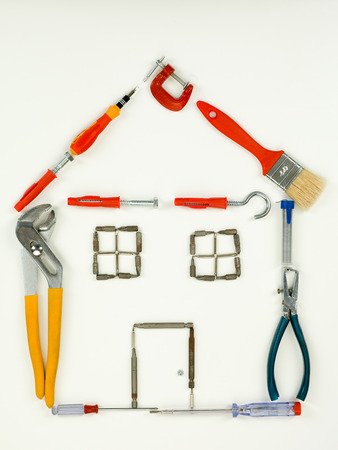 homeownership: outline of house made with household and construction tools, on white background. top view Stock Photo