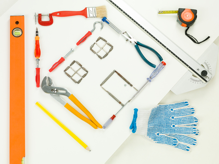 homeownership: shape of house made with household and construction tools, on white background. perspective view