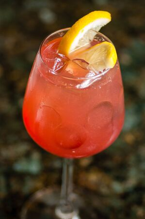 torrid: close-up of one misty wine glass filled with red liquid and ice cubes, decorated with two lemon wedges, on a blurry earth abd leaves background