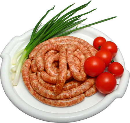 white plate containing uncoocked sausages with raw bunch onion and cherry tomatoes on the side Stock Photo