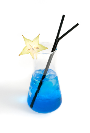straws: close-up of enlermeyer glass filled with a blue liquid, with ice cubes and two black straws, decorated with a carambola fruit slice, on a white background
