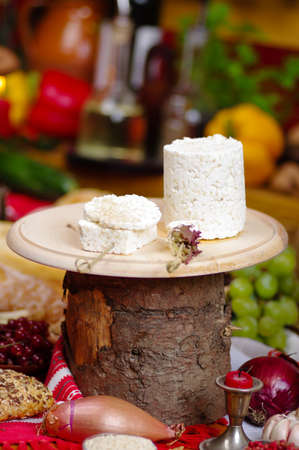 close-up of pieces of cheese on a knife board on a rustic background, with uncooked fruit and vegetables around