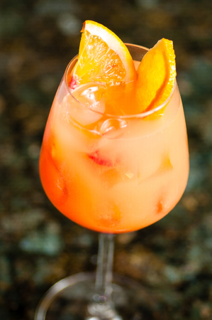torrid: close-up of a misty wine glass filled with orange gradient opaque liquid and ice cubes, decorated with two orange wedges, on a blurry earth and leaves background Stock Photo