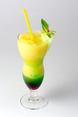 deceiving: descending close-up of a hurricane glass filled with a layered fruit cocktail, with purpple and green syrup on the bottom, decorated with a melon wedge and a yellow straw, on a gray background