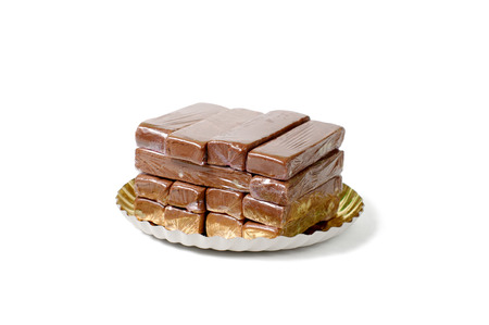 abstinence: close-up of a stack of fudge, wrapped individually in cellophane, on a plate with golden coating, on a white background Stock Photo