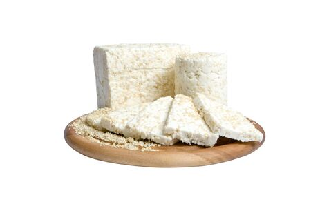 queso fresco blanco: front close-up of two pieces and slices of cheese with sesame seeds, on a wooden cutting board, on a white background