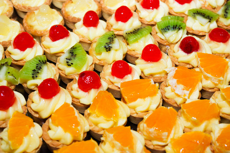 depending: close-up of small fruit tarts arranged in rows depending on the fruit, pineapple, kiwi, cherry and orange Stock Photo