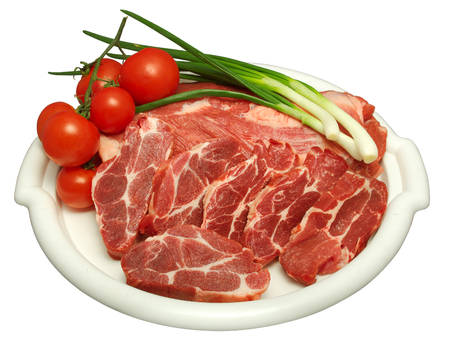 deceiving: white plate containing raw beef with white strains of fat, strains of bunch onion and cherry tomatoes on the side
