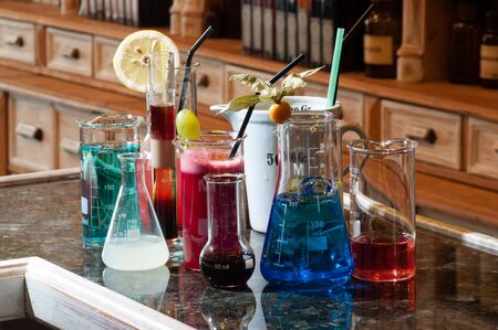 inebriated: close-up of several chemistry containers, filled with different colorful beverages, placed on top of a counter in front of apothecary wooden cabinets, containing different bottles and jars