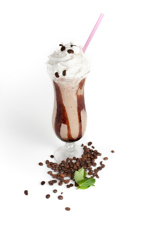 glass topped: close-up of tall hurricane glass, with coffee beans and two mint leaves around, filled with a brown, thick and opaque beverage, topped with whipped cream, decorated with coffee beans and a pink straw