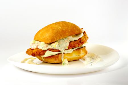 schnitzel sandwich with mustard mayonnaise tartar sauce on a white plate