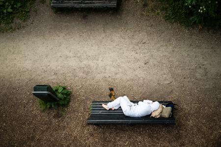 gente durmiendo: El hombre sin hogar vestido blanco limpio en reposo en un banco en el parque bajo la cabeza de equipaje