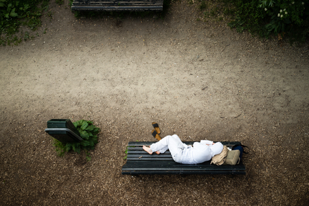restfulness: Homeless man dressed clean in white resting on a bench in the park  luggage under head Stock Photo