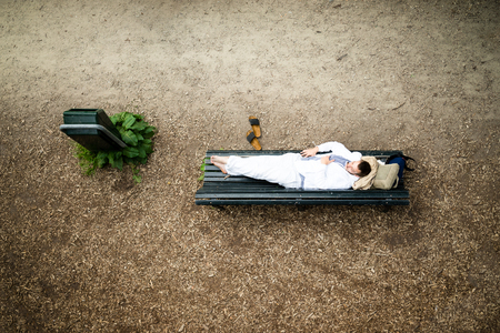 restfulness: casual dressed man resting on a bench in the park lying on the bench in nature Stock Photo