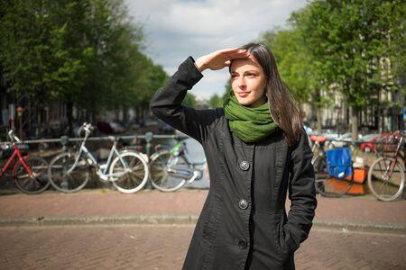 Schöne junge Frau auf einer Brücke, die Schönheit von Amsterdam bewundern ihre Augen von der Sonne mit der Hand schützen im schwarzen Mantel und grünen Schal gekleidet