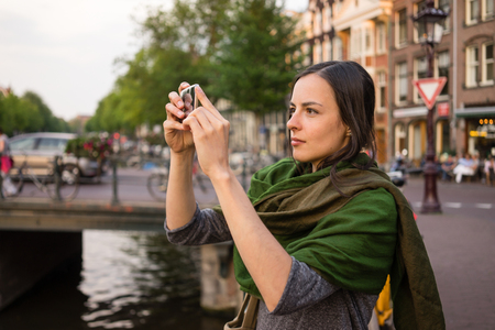 spent: beautiful young woman takes pictures in vacation spent in Amsterdam Stock Photo