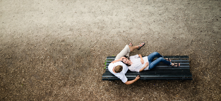 lap: Beautiful young woman lies on a bench in the park with his dead in his boyfriend lap smilling Stock Photo