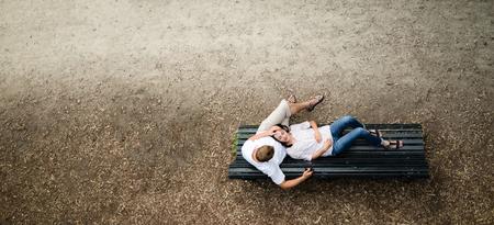 Schöne junge Frau liegt auf einer Bank im Park mit seinem tot in seinem Freund Schoß smilling