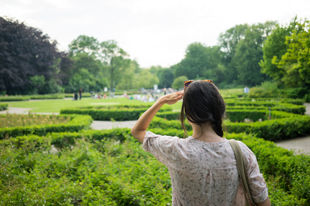 young woman rear view  watch the beauty of the Vondelpark in Amsterdam  hand to head sunny day