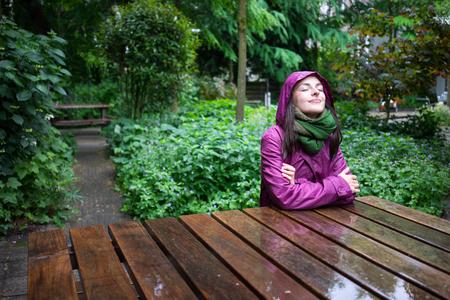 Hermosa mujer joven disfrutar de la lluvia en un jardín decorado con los ojos cerrados se sienta mesa de madera Foto de archivo