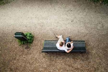banc de parc: Caucasien, jeune couple assis sur un banc de parc l'homme de prot�ger sa petite amie avec amour Banque d'images