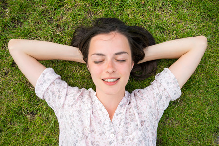 woman lying: beautiful young woman relaxing on green grass with hands under head and eyes closed