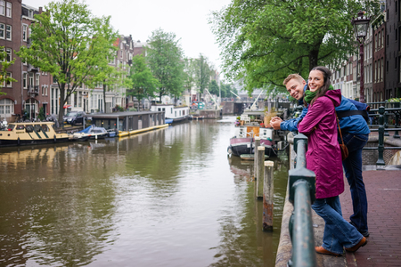 rains: Young couple Cucazian enjoy the beauty of Amsterdam, even if it rains Stock Photo