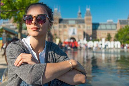 beauties: beautiful young woman traveler sitting on the waters edge admire Amsterdam Vondelpark beauties