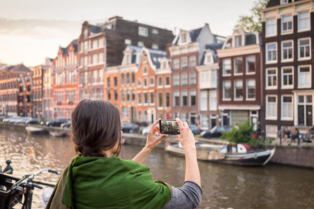 spent: beautiful young woman takes pictures in vacation spent in Amsterdam with beautiful architecture